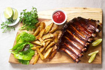 Homemade baked meat ribs served with french fries, herbs, lime and ketchup on a wooden board. Rustic style.