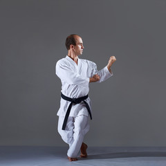 On a gray background, an active adult athlete trains formal karate exercises.