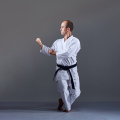 Over gray background active adult athlete doing formal karate exercises.