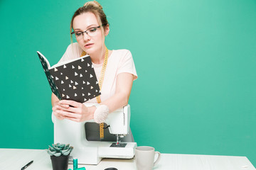 Sewing workshop. Seamstress at work. Portrait of a young dressmaker with notebook on a colored background.