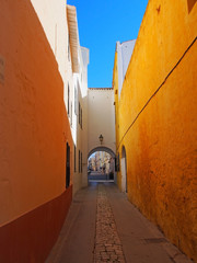 a long narrow alley in ciutadella town menorca with a bright yellow wall and archway at the end with a blue summer sky