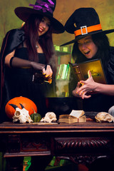 Photo of two witches brunettes in black hats brewing potion