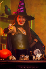 Image of young witch in black hat with outstretched hand with magic wand and cauldron