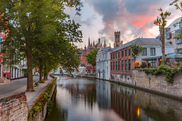 Scenic cityscape with a medieval tower Belfort and the Green canal, Groenerei, at sunset in Bruges, Belgium
