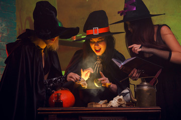 Picture of three witches in hats with book of potions making potions in cauldron