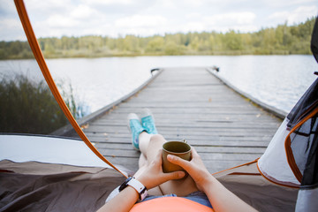 Image of woman with iron mug in hands sitting on wooden bridge by river