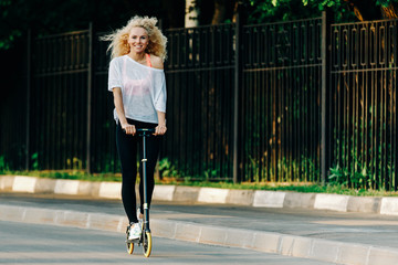 Full-length photo of curly-haired athletic woman kicking on scoo