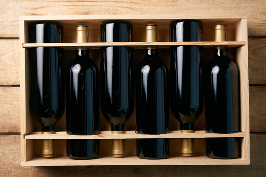 Wine bottles in wooden crate on wood table background, close-up.
