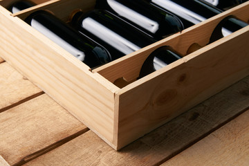 Six wine bottles collection in wooden box on wood table backgrou
