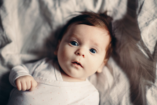Closeup portrait of cute adorable funny white Caucasian brunette little baby newborn with blue grey eyes lying on bed looking in camera. Authentic lifestyle candid real life.Toned with film filters.