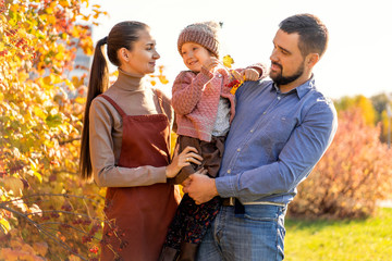 family walking in autumn park at sunset