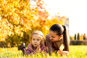 mother with daughter in love walking in autumn park