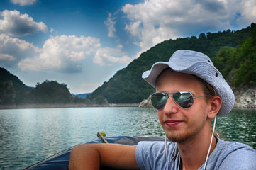 Tourist wearing a hat sitting in the pontoon, sailing on Zaovine Lake in Serbia