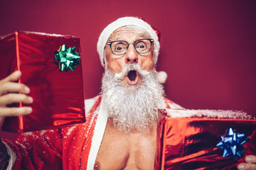 Happy fit santa claus laughing and giving christmas gifts - Trendy beard tattoo hipster senior wearing xmas clothes and holding presents - Celebration and holidays concept