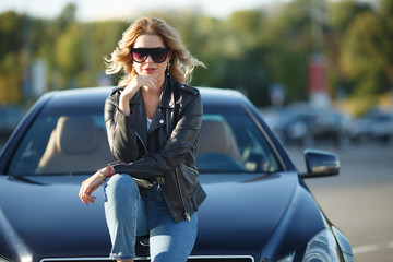 Photo of young blonde in sunglasses sitting on hood of black car