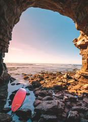 Red Surfboard Abandoned Along a Coastal Cave, San Diego, California