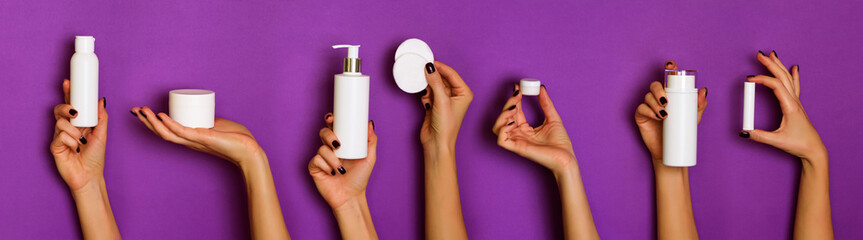 Female hands holding white cosmetics bottles - lotion, cream, serum on violet background. Banner. Skin care, pure beauty, body treatment concept