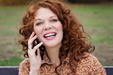 jeune et jolie femme rousse téléphonant avec téléphone portable dans un parc