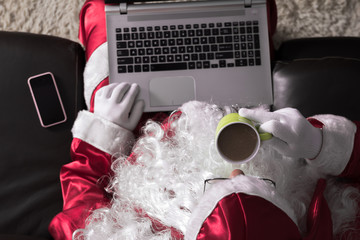 Top view of Santa Claus sitting in couch at home using laptop for communication and leisure. Drinking a latte drink.