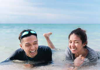 Happy young asian couple  lying on tropical beach in southeast asian,people having fun.
