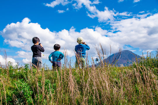 大山を眺めたり、写真を撮る子どもたち Three boys are watching and taking pictures of Mt. Daisen, Japanese famous mountain