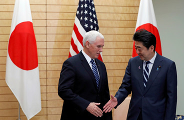 Japanese Prime Minister Shinzo Abe reaches out to shake hands with U.S. Vice President Mike Pence at Abe's official residence in Tokyo, Japan