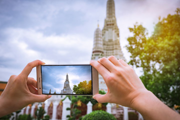 women hand taking photos With a smartphone at the Wat Arun temple on vacation Bangkok Thailand.