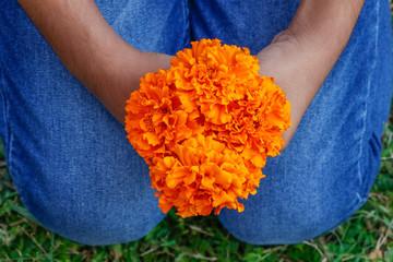 Little girl holding yellow marigold flower bouquet