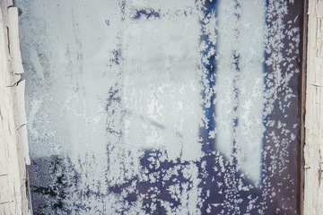 Old window glass covered with ice frost in winter