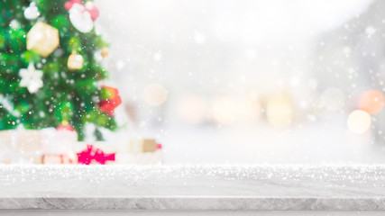 Empty white marble stone table top with bokeh light on blurred Christmas tree banner background with snowfall - can be used for display or montage your products.