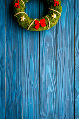 Christmas wreath traditional, classic type. Wreath made of spruce branches and red ribbons on blue wooden background top view space for text