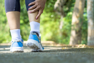 female runner hand holding leg pain from exercise over trained concept