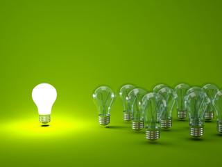 Bright light bulb on green background