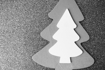 Festive Christmas Christmas winter happy beautiful beautiful black and white background with a small toy wooden homemade cute Christmas tree. Flat lay. Top view. Holiday decorations