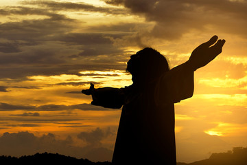 Silhouette of Jesus christ standing with raised arms