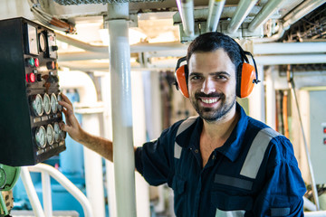 Marine engineer officer in engine control room ECR. Seamen's work. He starts or stops main engine of ship Wall mural