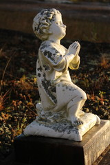 Little cherub statue on a grave of a child.
