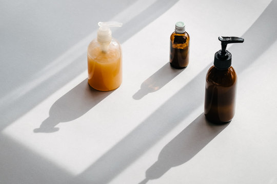 Clear plastic and glass brown bottles with organic cosmetics from above. Direct light. Beauty blogging minimalism concept