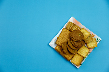Different types of cookies on a colored square plate on a blue isolated background. View from above