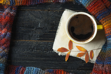 A mug of hot coffee or chocolate on a dark table with dry leaves and copy space. Winter or autumn composition
