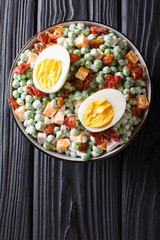 English salad of fresh green peas with eggs, bacon and cheese dressed with cream sauce close-up in a bowl. Vertical top view
