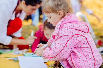 Cute little child girl learn to drawing, children painting in the park. The concept of a happy family.