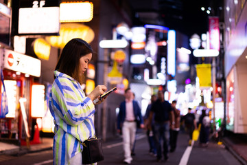 A woman is shopping online at the night street.