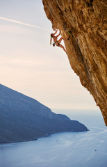 Young female rock climber on challenging route on cliff