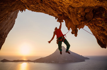 Male rock climber hanging on cliff with one hand at sunset Wall mural