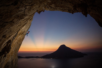 Male rock climber on overhanging cliff at sunset, with beautiful view of island in background