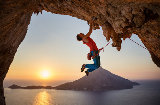 Male rock climber hanging with one hand on challenging route at sunset