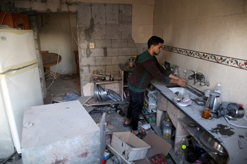 Palestinian washes his hand inside the kitchen of his house that was damaged in an Israeli air strike, in Gaza City