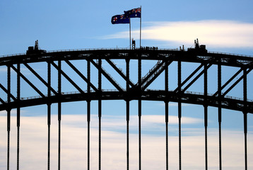Tourists stand atop of the Sydney Harbour Bridge next to flag poles flying the New South Wales state and Australian national flags in Sydney