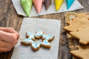 Making Christmas gingerbread at home. Female hand decorates star-shaped gingerbread with colored icing.